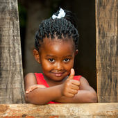 Little african girl at wooden fence with thumbs up. — Stock Photo