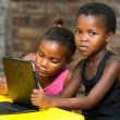 Two african girls sitting at table with tablet. — Stock Photo