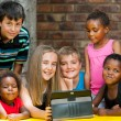 Stock Photo: Bunch of kids playing on tablet.