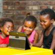 Three african kids playing together on tablet. — Stock Photo