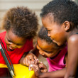 Threesome african kids having fun with tablet. — Stock fotografie