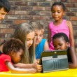 Stock Photo: Diverse group of kids looking at tablet.