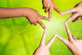 Kids joining fingers forming a star. — Stock Photo