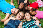 Diverse group og children laying together on grass. — Stock Photo