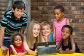Bunch of kids playing on tablet. — Stock Photo