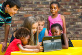 Diverse group of kids looking at tablet. — Stock Photo