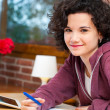 Cute student sitting at table with homework. — Stock Photo