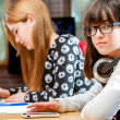 Cute girl with friends at schoolwork table. — Stock Photo #41550987