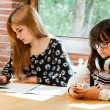 Stock Photo: Two girls concentrating with schoolwork.