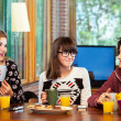 Stock Photo: Three girls having breakfeast at home.