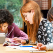 Three young students working on digital divices. — Stock Photo #41551051