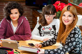 Portrait of three young female students at desk. — Stock Photo