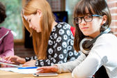 Cute girl with friends at schoolwork table. — Foto de Stock