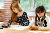 Two girls concentrating with schoolwork. — Stock Photo