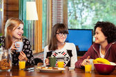 Three girls having breakfeast at home. — Stock Photo