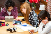 Three students working on digital devices. — Stock Photo