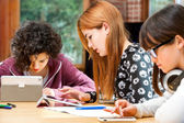 Three young students working on digital divices. — Stock Photo