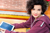 Cute girl sitting at desk with tablet. — Stock Photo