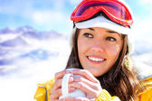 Female skier drinking coffee. — Stock Photo