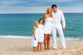 Family in white on beach. — Stock Photo