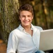 Portrait of teen boy against tree. — Stock Photo