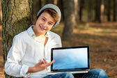 Teen student pointing at blank laptop screen. — Stock Photo