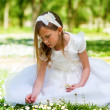 Sweet girl in white dress picking flowers. — Stock Photo