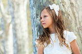 Girl in white standing next to tree. — Stock Photo