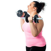 Side view of obese girl doing workout. — Stock Photo