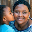 African girl kissing mother on cheek. — Stock Photo #48678787