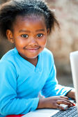 Cute african girl typing on laptop. — Stock Photo