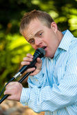 Handicapped boy singing on microphone. — Stock Photo