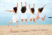 Teen girls jumping on beach — Stock Photo