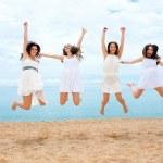 Four girlfriends jumping on beach — Stock Photo #50431857