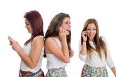 Threesome teen girls talking on smart phones — Stock Photo