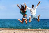 Teen couple jumping giving backs — Stock Photo