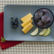 Cheese and fruit plate with red napkin — Stock Photo #12441112