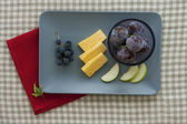 Cheese and fruit plate with red napkin — Stock Photo