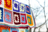 Hanging handmade crochet blanket dry on air selective focus — Stock Photo