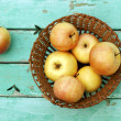 Rustic still life with apples on basket on turquoise weathered w — Stock Photo #19656717