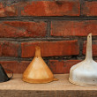 Three old fashioned funnels from metal and plastic on rustic woo — Zdjęcie stockowe