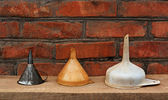 Three old fashioned funnels from metal and plastic on rustic woo — Stock Photo