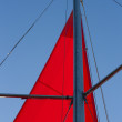 Part of red triangle sail on a vibrant blue sky — Stock Photo