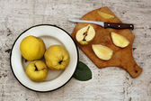 Rural still life ripe yellow quince fruits on the plate and cut — Stock Photo