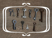 Old fashioned keys on wooden aged background with frame concept — Stock Photo