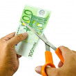 Euro money being cut in two with scissors - Stock Photo