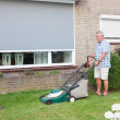 Dutch senior mowing lawn — Stock Photo