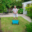 Senior fertilising the lawn - Stock Photo