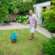 Senior fertilising the lawn — Stock Photo