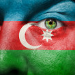 Flag painted on face with green eye to show Azerbaijan support — Stock Photo